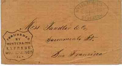 A buff colored envelope with blue Wells Fargo, Stockton and a black Hunter, Mud Springs hand stamp on the front of the envelope. Addressed to Tandler & Co. in San Francisco.